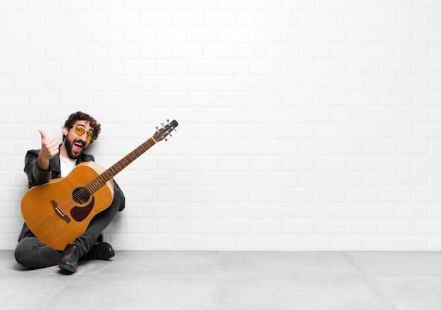Jonge muzikant man voelt zich trots, zorgeloos, zelfverzekerd en gelukkig, glimlachend positief met duimen omhoog met een gitaar