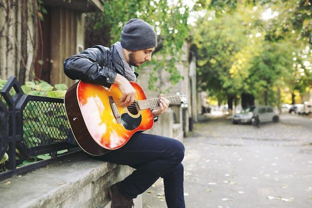 Jonge muzikant met gitaar in stad