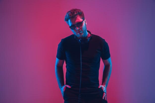 Jonge muzikant met koptelefoon in neonlicht