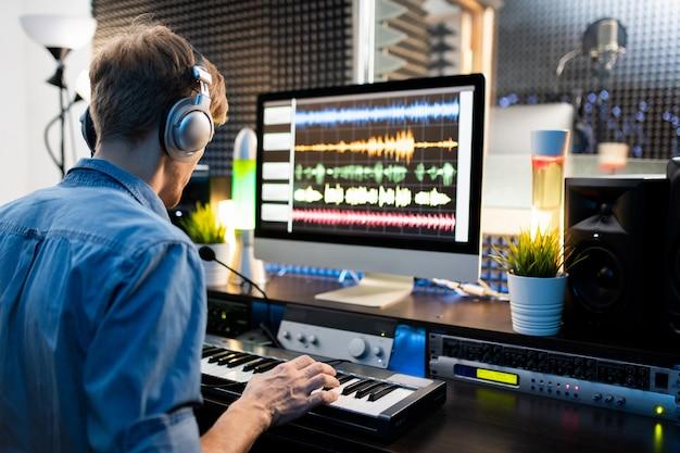 Jonge muzikant met koptelefoon op toetsen van piano klavier te drukken zittend door computermonitor en werken met geluiden