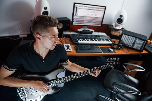 Jonge muzikant neemt basgitaar binnenshuis op in de studio.