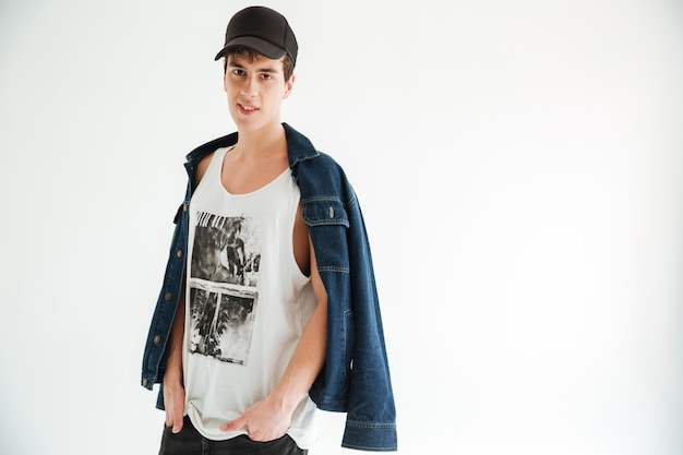 Jonge mysterieuze man in cap en spijkerjasje