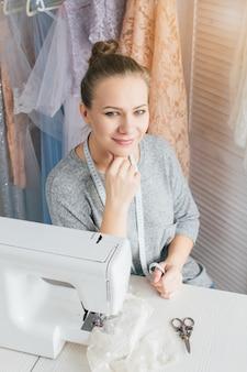 Jonge naaister die aan naaimachine werkt