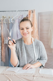 Jonge naaister maakt kleding stof snijden