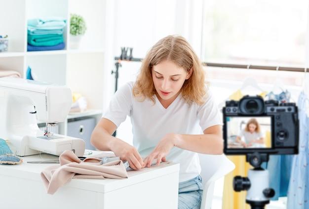 Jonge naaister meetdoek voor nieuw ontwerp in werkplaats
