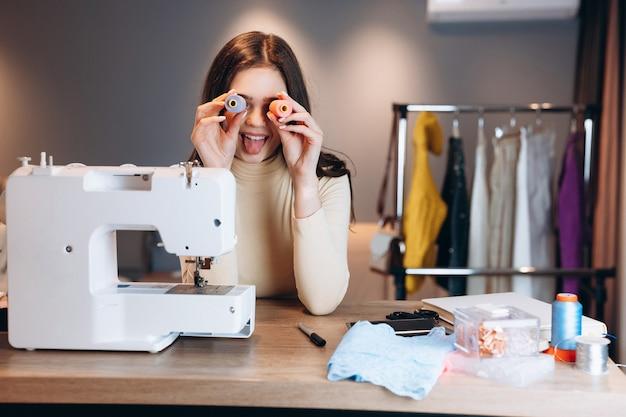 Jonge naaister vrouw met naaimachine. naaister die ogen bedekt met draden in werkplaats. het maken van online cursussen voor kledingontwerp.