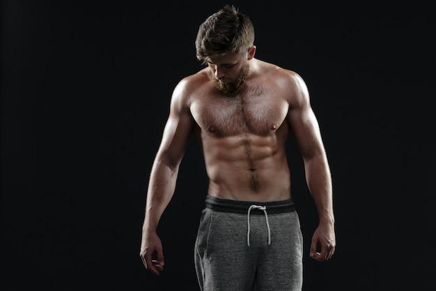 Jonge naakte atletische man. geïsoleerde donkere achtergrond
