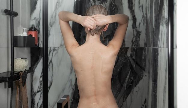 Jonge naakte dame neemt thuis een douche, uitzicht vanaf de achterkant. waterstromen stromen langs de huid.