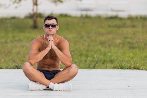 Jonge naakte man in zonnebril en witte sneakers zittend op een houten vloer in de straat met zijn benen gekruist.