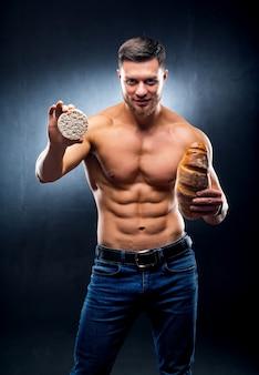 Jonge naakte torso man met granen cracker en brood. kiezen tussen gezond en schadelijk voedsel. verticale foto. grijze achtergrond. detailopname