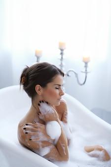 Jonge naakte vrouw die een ontspannend schuimend bad neemt