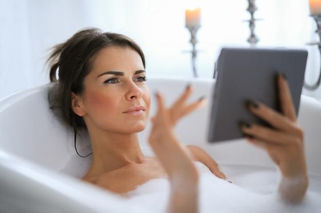 Jonge naakte vrouw die een ontspannend schuimend bathand neemt met behulp van digitale tablet