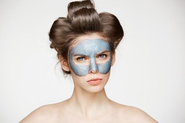 Jonge naakte vrouw in haarkrulspelden en gezichtsmasker fronsen. schoonheid huidverzorging en cosmetologie.