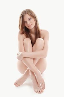 Jonge naakte vrouw zittend op de vloer, lichaam en huidverzorging concept