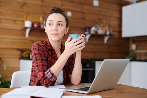 Jonge nadenkend freelancer met mok met drankje zittend aan de keukentafel voor laptop en geïnspireerd te raken