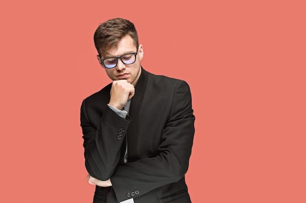 Jonge nadenkende knappe man in zwart pak en glazen geïsoleerd op rode studio achtergrond