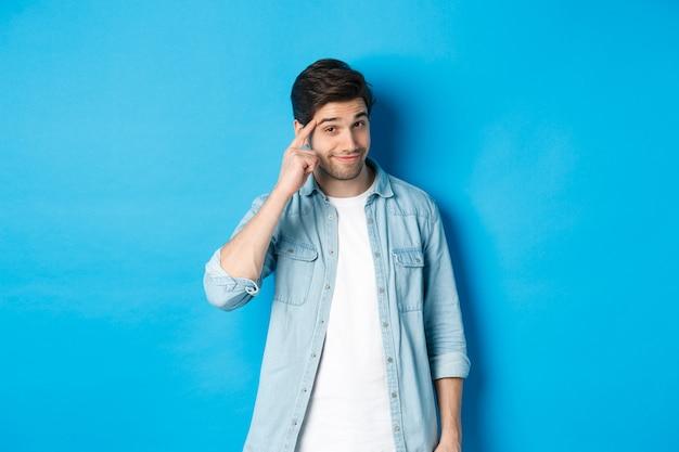 Jonge nadenkende man die naar het hoofd wijst, erover nadenkt, een hint geeft, in vrijetijdskleding op een blauwe achtergrond staat