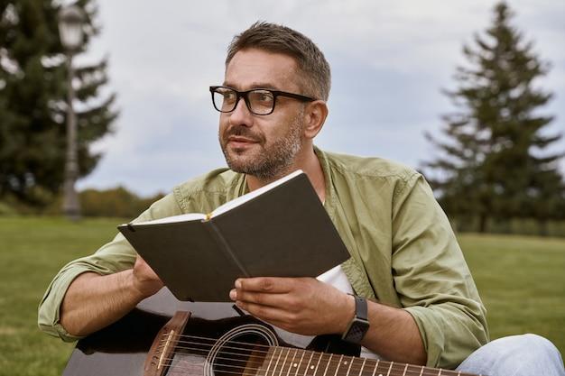 Jonge nadenkende man met een bril die akoestische gitaar vasthoudt en zittend een lied componeert