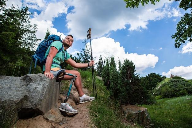 Jonge nadenkende vermoeide man zittend op de steen terwijl hij uitrust na het wandelen