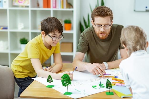 Jonge natuurliefhebbers. attente geïnspireerde bebaarde leraar die zijn leerlingen helpt met handgemaakte poster terwijl ze allemaal samen zitten sitting