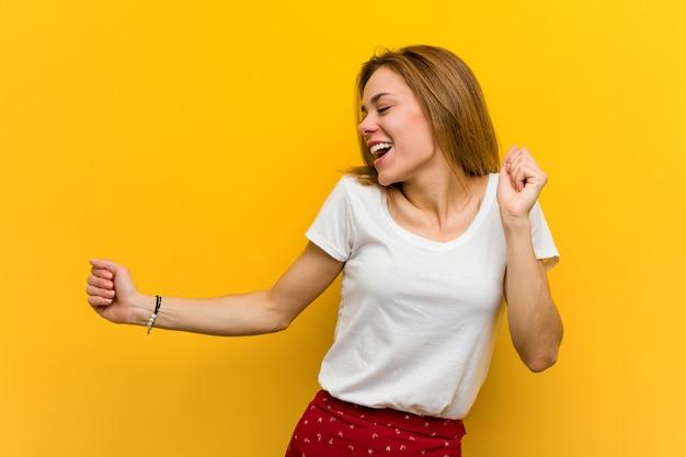 Jonge natuurlijke blanke vrouw dansen en plezier maken.