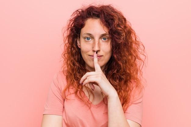 Jonge natuurlijke en authentieke redhead vrouw die een geheim houdt of om stilte vraagt.
