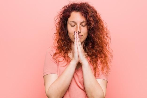 Jonge natuurlijke en authentieke roodharige vrouw die hand in hand bidt in de buurt van de mond, voelt zich zelfverzekerd.