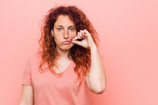 Jonge natuurlijke en authentieke roodharige vrouw met vingers op lippen die een geheim bewaren.