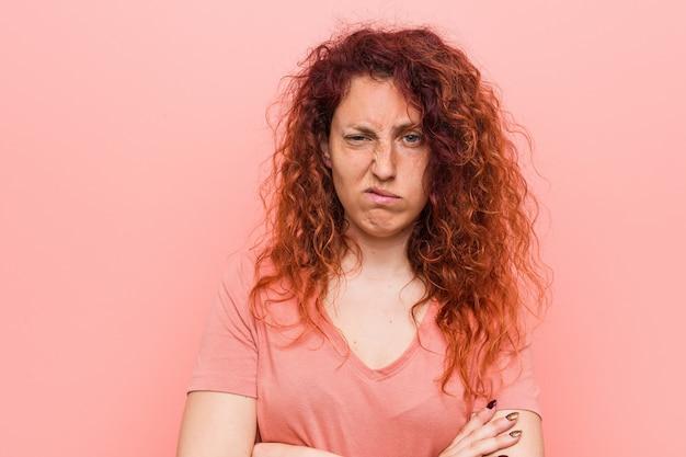Jonge natuurlijke en authentieke roodharige vrouw ongelukkig kijken in de camera met sarcastische uitdrukking.