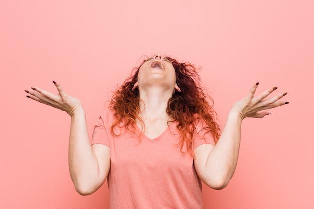 Jonge natuurlijke en authentieke roodharige vrouw schreeuwen naar de hemel, op zoek, gefrustreerd