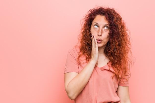 Jonge natuurlijke en authentieke roodharige vrouw zegt een geheim heet remmend nieuws en kijkt opzij