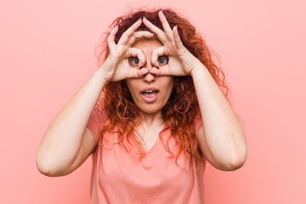 Jonge natuurlijke en authentieke roodharigevrouw die ok teken over ogen tonen