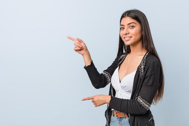 Jonge natuurlijke en mooie arabische opgewekte vrouw het richten met wijsvingers weg.