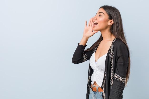 Jonge natuurlijke en mooie arabische vrouw die en palm schreeuwen dichtbij geopende mond houden.