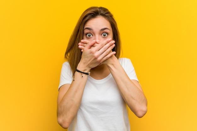 Jonge natuurlijke kaukasische geschokte vrouw behandelend mond met handen.