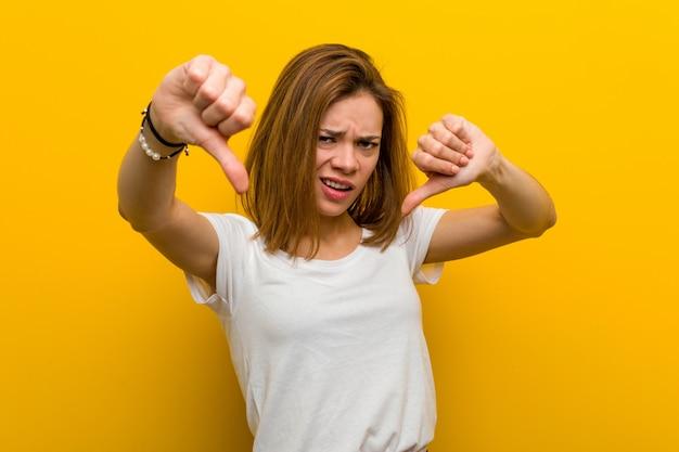 Jonge natuurlijke kaukasische vrouw die duim tonen en afkeer uitdrukken.