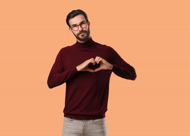 Jonge natuurlijke man doet een hartvorm met handen