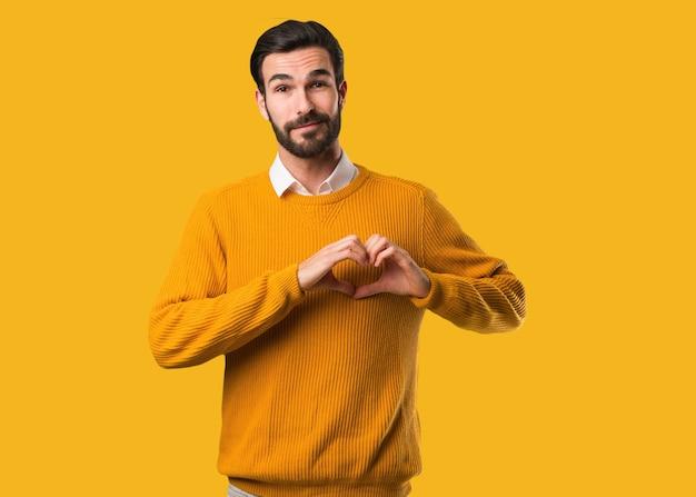 Jonge natuurlijke mens die een hartvorm met handen doet