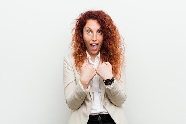 Jonge natuurlijke redhead bedrijfsvrouw verraste het richten met vinger, breed glimlachend.