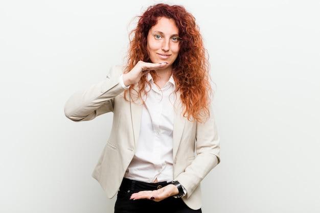 Jonge natuurlijke roodharige bedrijfsdievrouw tegen witte achtergrondholding iets met beide handen wordt geïsoleerd, productpresentatie.