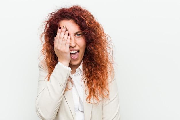 Jonge natuurlijke roodharige bedrijfsvrouwenachtergrond die pret hebben die de helft van gezicht behandelen met palm.