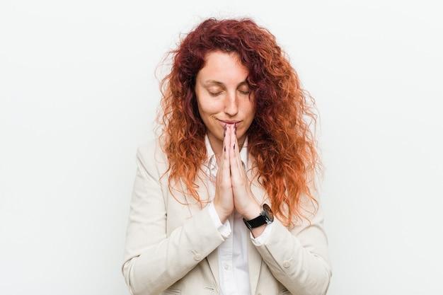 Jonge natuurlijke roodharige zakenvrouw geïsoleerd tegen een witte achtergrond hand in hand bidden in de buurt van de mond, voelt zich zelfverzekerd.
