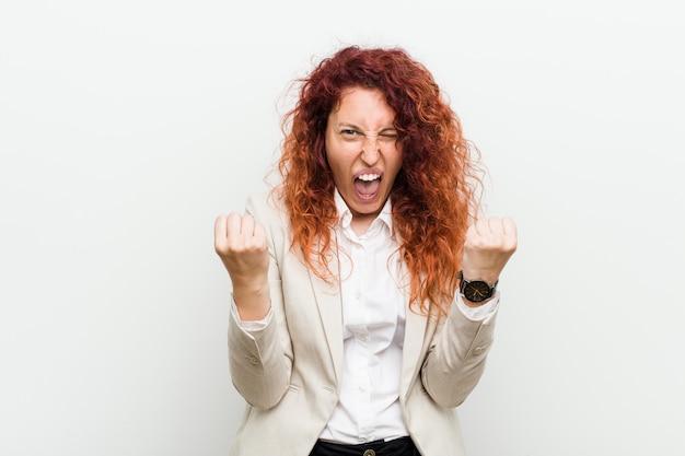 Jonge natuurlijke roodharige zakenvrouw geïsoleerd tegen wit zorgeloos en opgewonden gejuich. overwinning concept.