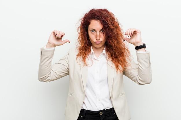 Jonge natuurlijke roodharige zakenvrouw geïsoleerd tegen witte achtergrond voelt zich trots en zelfverzekerd, voorbeeld te volgen.