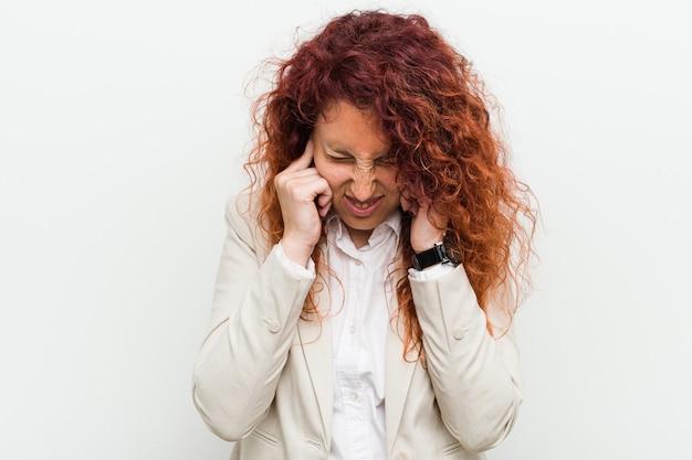 Jonge natuurlijke roodharige zakenvrouw geïsoleerd tegen witte muur die oren bedekt met handen.