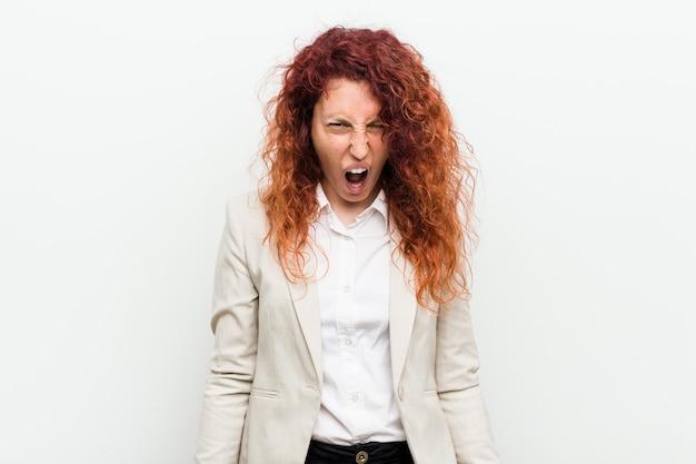 Jonge natuurlijke roodharige zakenvrouw geïsoleerd tegen witte muur schreeuwen erg boos en agressief.