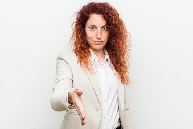 Jonge natuurlijke roodharige zakenvrouw geïsoleerd tegen witte muur uitrekkende hand