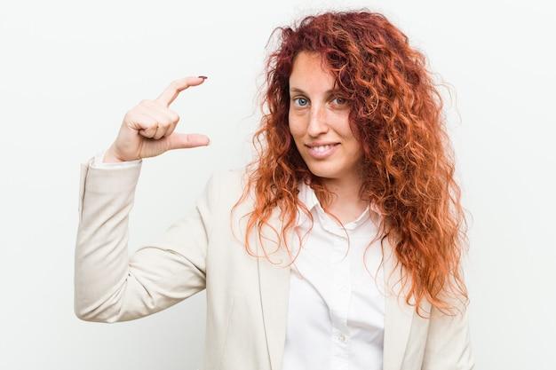 Jonge natuurlijke roodharige zakenvrouw houden iets kleins met wijsvingers, glimlachen en zelfverzekerd