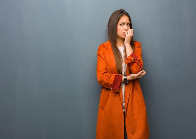 Jonge natuurlijke vrouw bijt nagels, nerveus en erg angstig