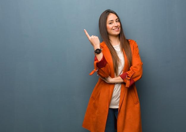 Jonge natuurlijke vrouw die aan de kant met vinger richt